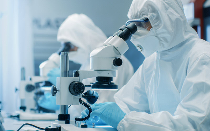 Manufacturing Engineers in Cleanroom Suits Using Microscopes - SIPMM